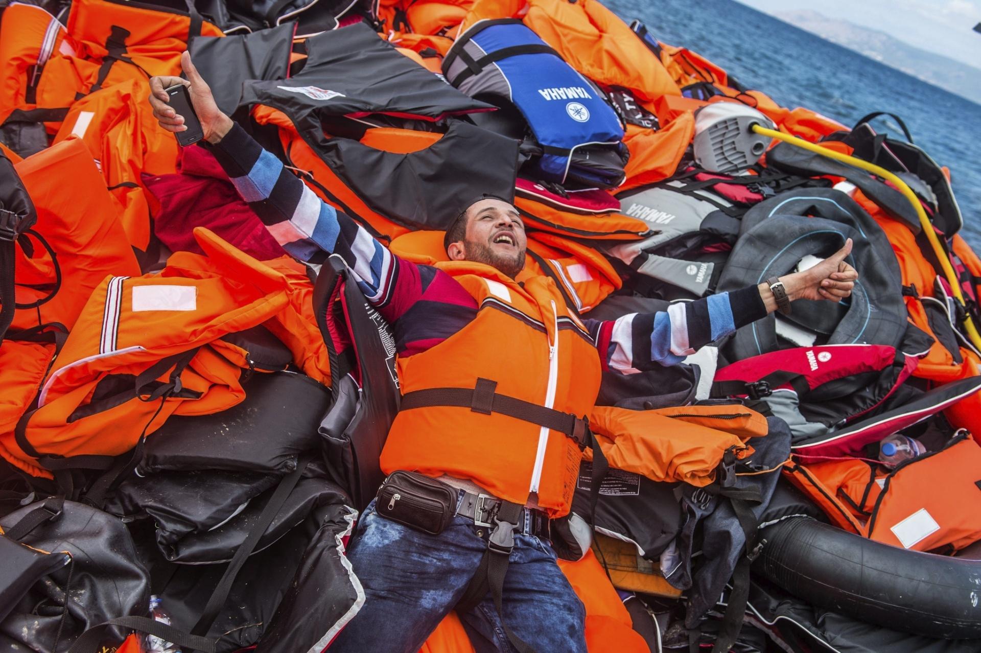 2.out.2015 - Imigrante celebra chegada a salvo em cima de um monte de coletes salva-vidas depois de pegar um bote para alcançar a ilha de Lesbos, na Grécia