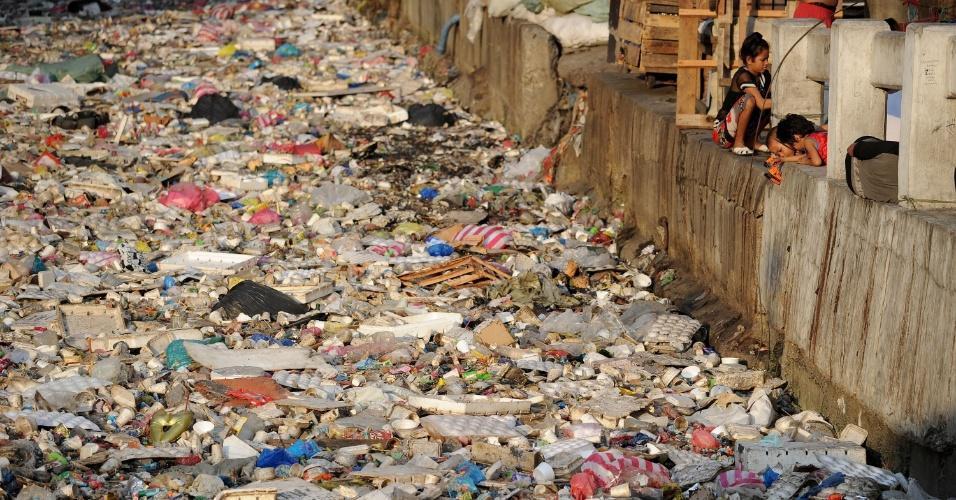 23.jan.2016 - Crianças brincam perto de um rio com excesso de lixo em Manila, nas Filipinas. Nesta semana, uma pesquisa mostrou que os oceanos terão mais lixo plástico do que peixes até 2050, a não ser que medidas sejam tomadas para reciclar os materiais