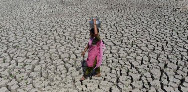 Mulher caminha por área de seca onde estava localizado o lago Chandola, em Ahmedabad, na Índia. Onda de calor que atinge o país destruiu colheitas e deixou centenas de mortos em pelo menos 13 Estados