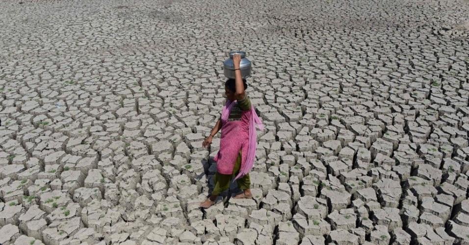 20.mai.2016 - Mulher caminha pelo leito seco do lago Chandola, em Ahmedabad, na Índia. A onda de calor que atinge o país destruiu a colheita e deixou centenas de mortos em pelo menos 13 Estados. A cidade de Phalodi registrou a maior temperatura da Índia, 51º Celsius. O Departamento Meteorológico do país informou que o recorde anterior era de 50,6ºC, registrados em 1996, em Alwar, no Rajastão