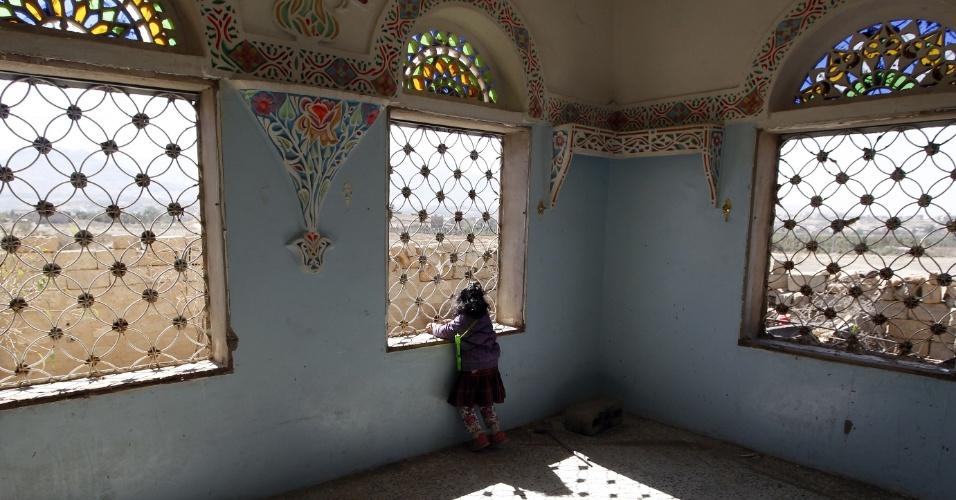 15.nov.2016 - Menina olha pela janela de casa destruída por forças sauditas no subúrbio de Sanaa, capital do Iêmen