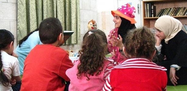 """A jordaniana Rana Dajani, idealizadora do programa We Love Reading (""""nós amamos ler""""), lê para crianças refugiadas"""