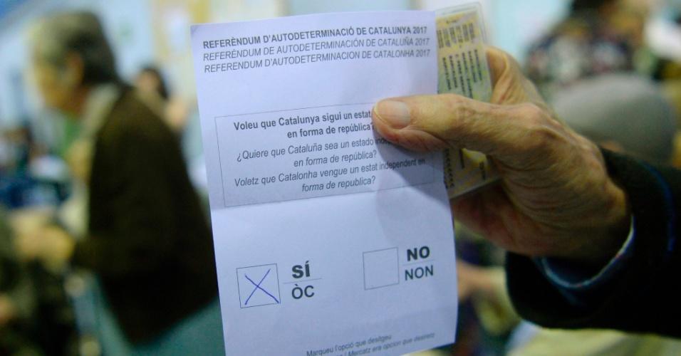 1.out.2017 - Homem se prepara para depositar sua cédula de votação em posto de votação localizado em Barcelona