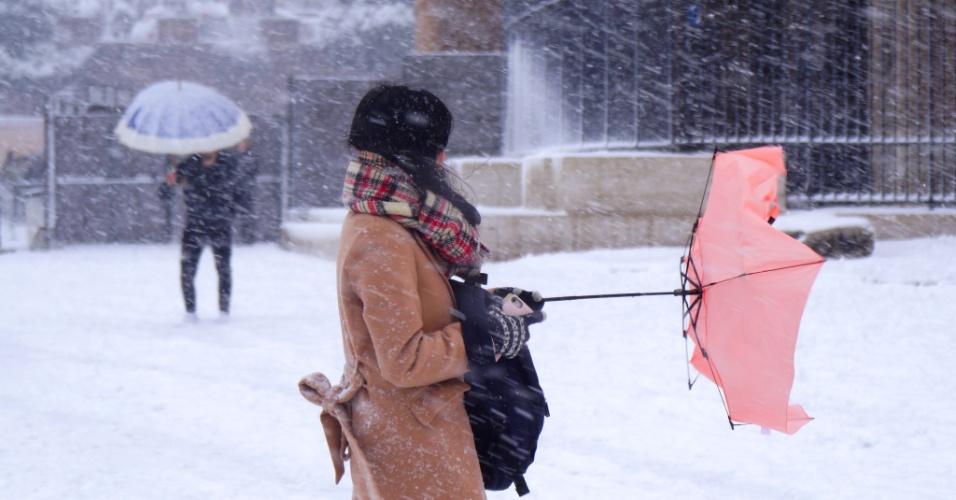 26.fev.2018 - Nevasca arrasta guarda-chuva de mulher, em Roma, Itália