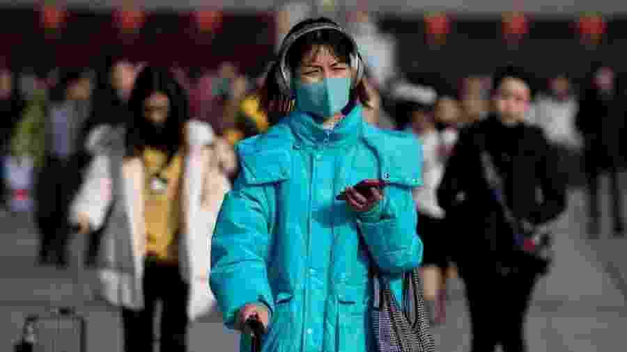 Chineses usam máscaras para tentar evitar a propagação do novo vírus que já matou 6 pessoas no país - AFP