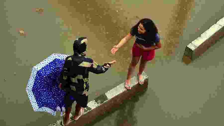 Pessoas tentam atravessar trecho alagado da Marginal do Tietê, em São Paulo, por cima de canteiros - CELSO LUIX/FUTURA PRESS/FUTURA PRESS/ESTADÃO CONTEÚDO