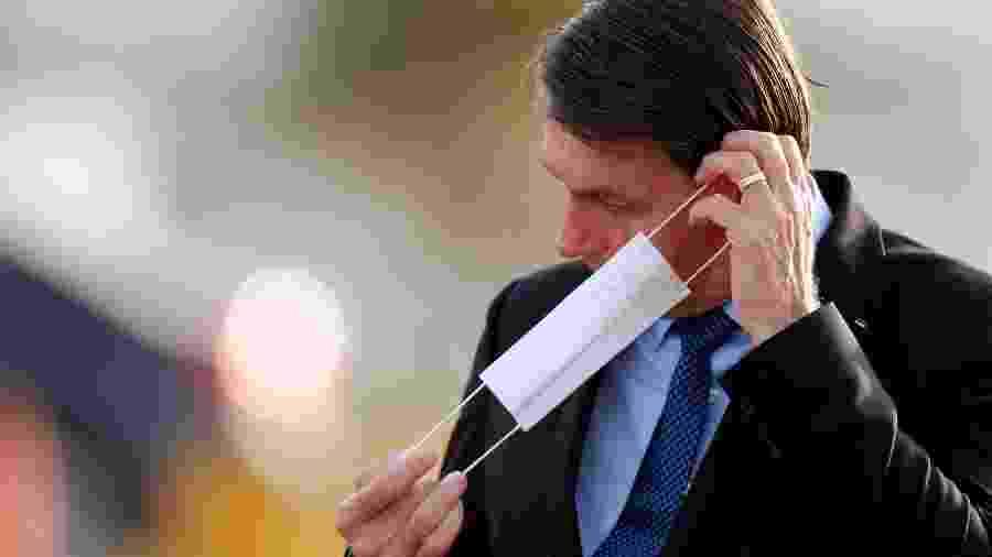 O presidente Jair Bolsonaro coloca máscara de proteção em Brasília - Adriano Machado/Reuters