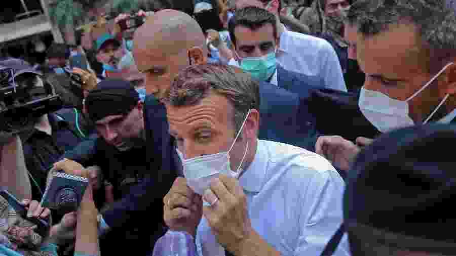 Presidente Emmanuel Macron ajusta máscara durante sua visita a Beirute, acompanhada por uma multidão - AFP