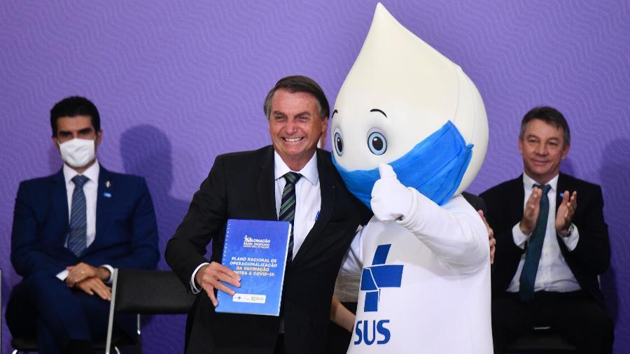 16.dez.2020 - O presidente Jair Bolsonaro, acompanhado do Zé Gotinha, personagem criado para as campanhas de vacinação do SUS, durante cerimônia de lançamento do plano nacional de vacinação contra covid-19 - Mateus Bonomi/AGI/Estadão Conteúdo