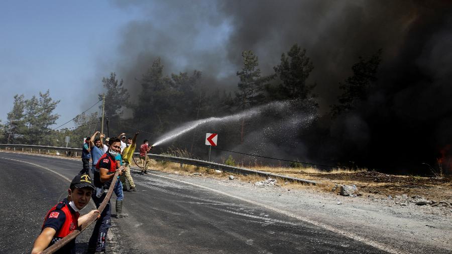 Bombeiros e voluntários tentam extinguir um incêndio florestal perto de Marmaris, na Turquia - EUTERS/Umit Bektas