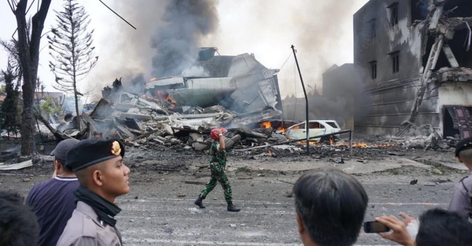 30.jun.2015 - Policiais e oficiais militares isolam local do acidente com um avião de transporte militar indonésio C-130 Hercules, em área residencial da cidade de Medan, na ilha de Sumatra, Indonésia. O acidente incendiou casas e veículos e matou mais de cem pessoas