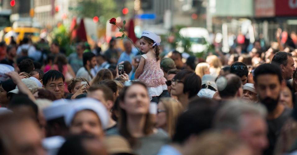 14.ago.2015 - Menina segura rosa e usa chapéu de marinheiro em uma multidão que assiste aos veteranos da Segunda Guerra Mundial Ray e Ellie Williams recriarem o beijo entre um marinheiro e uma enfermeira durante anúncio do fim da Segunda Guerra Mundial, na Times Square, em Nova York, retratada pelo fotógrafo Alfred Eisenstaedt. A icônica imagem completa 70 anos