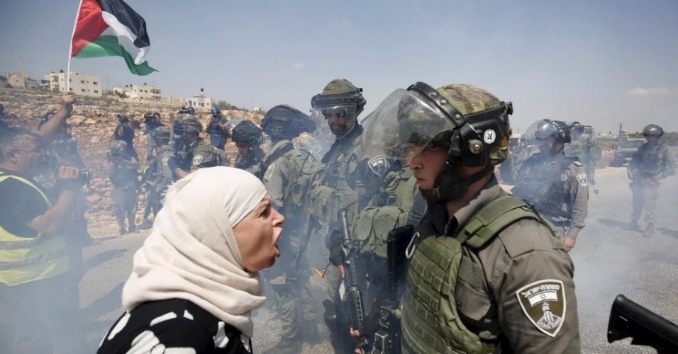 4.set.2015 - Palestina discute com um policial de fronteira israelense durante protesto contra os assentamentos judaicos na aldeia de Nabi Saleh, na Cisjordânia