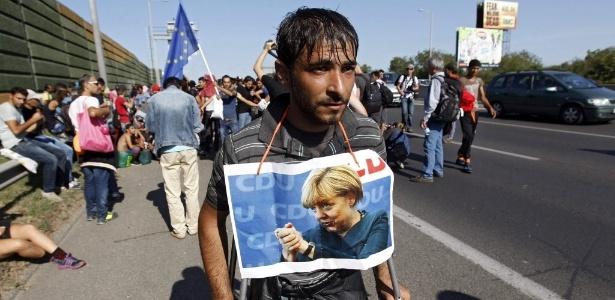 4.set.2015 - Refugiado usa imagem da chanceler alemã, Angela Merkel, pendurada no pescoço enquanto deixa Budapeste, na Hungria, em direção à Alemanha