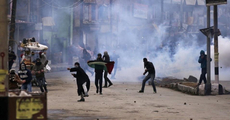 8.jan.2-15 - Manifestantes da região da Caxemira lançam pedras na direção da polícia indiana durante conflito em Srinagar, na Índia. No protesto, os ativistas pedem o fim do domínio indiano na região. A Caxemira está localizada parte na Índia e parte do Paquistão e é alvo de disputa entre os dois países