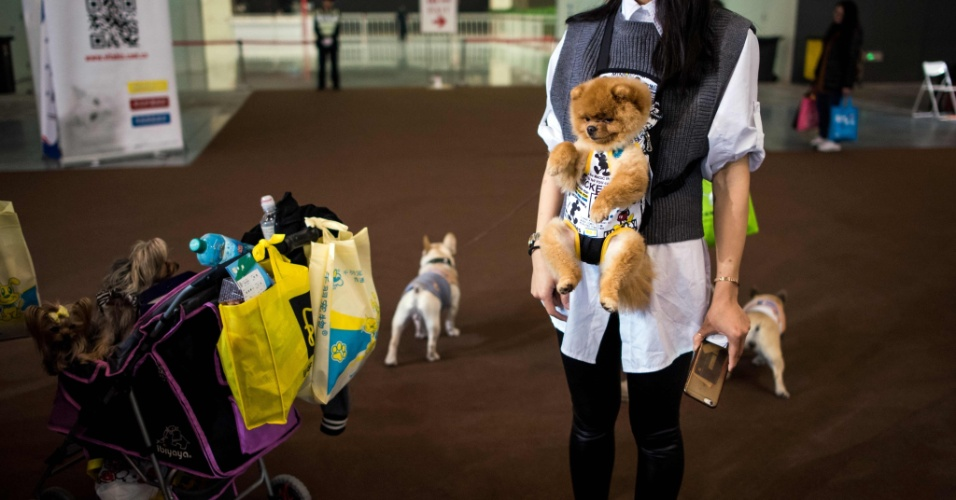 18.mar.2016 - Coleira para quê? Mulher carrega cachorro no seu corpo durante a Exposição Internacional de Pets em Xangai, na China