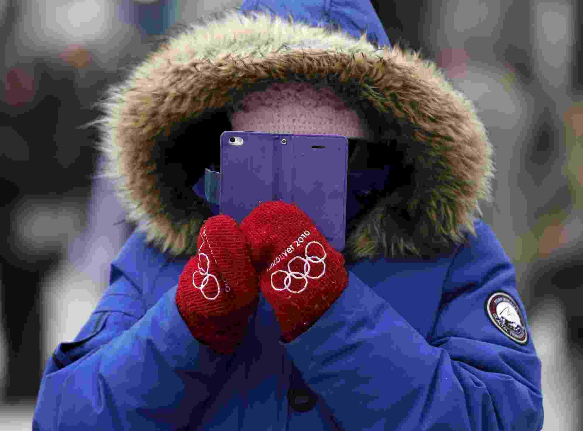 3.abr.2016 - Será que está frio no Canadá? Em plena primavera de Toronto, uma mulher bastante agasalhada fica completamente coberta por casacos enquanto tira foto com seu celular da parada anual que celebra o Dia da Independência da Grécia - undefined