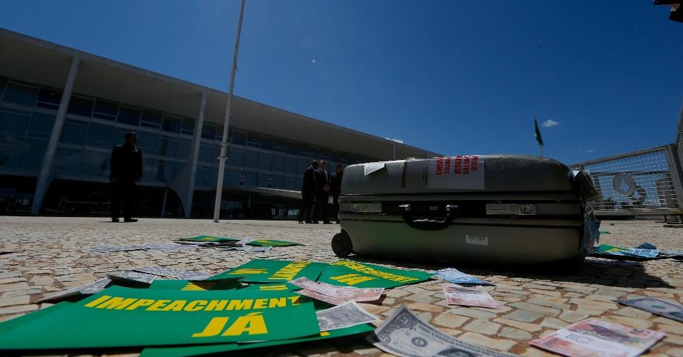 7.abr.2016 - Uma mala cheia de notas falsas foi colocada na frente do Palácio do Planalto durante protesto de parlamentares que fazem oposição ao governo