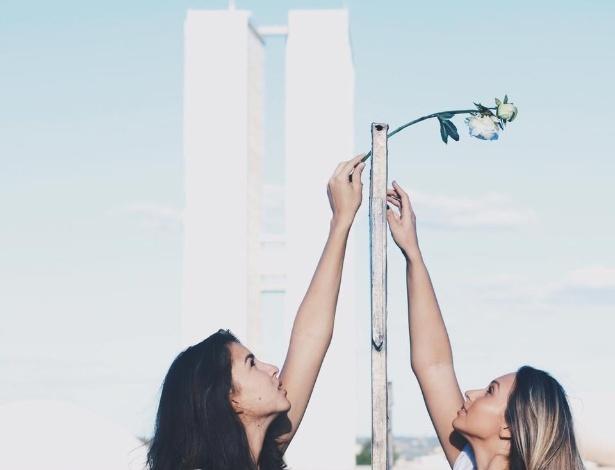 """15.abr.2016 - Jovens posam para foto passando uma rosa branca pelo """"muro da vergonha"""" instalado na Esplanada dos Ministérios, em Brasília, para separar manifestantes pró e contra o impeachment da presidente Dilma Rousseff"""