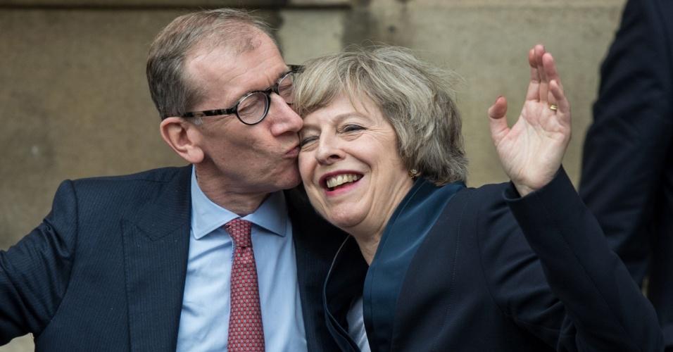11.jul.2016 - A futura primeira-ministra britânica Theresa May (dir) recebe um beijo do seu marido, Philip John May (esq), depois de conversar com a imprensa na entrada do Palácio de Westminster, em Londres. A antiga ministra do Interior substituirá David Cameron como premiê do país nesta quarta e terá como grande desafio a saída do Reino Unido da União Europeia
