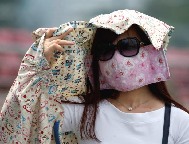 Mulher exagera na proteção contra a fumaça do incêndio florestal - Edgar Su/Reuters