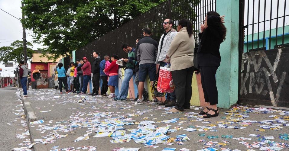 2.out.2016 - Eleitores aguardam em fila, cercados por santinhos espalhados pelo chão, para votar em uma escola da zona leste da cidade de São Paulo