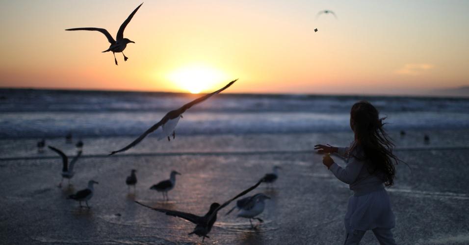 4.out.2016 - Menina joga migalhas de pão na praia de Venice durante oração Tashlich, um ritual Rosh Hashanah para lançar simbolicamente os pecados, durante a celebração do ano novo judaico da Comunidade Espiritual Nashuva, em Los Angeles, Califórnia (EUA)