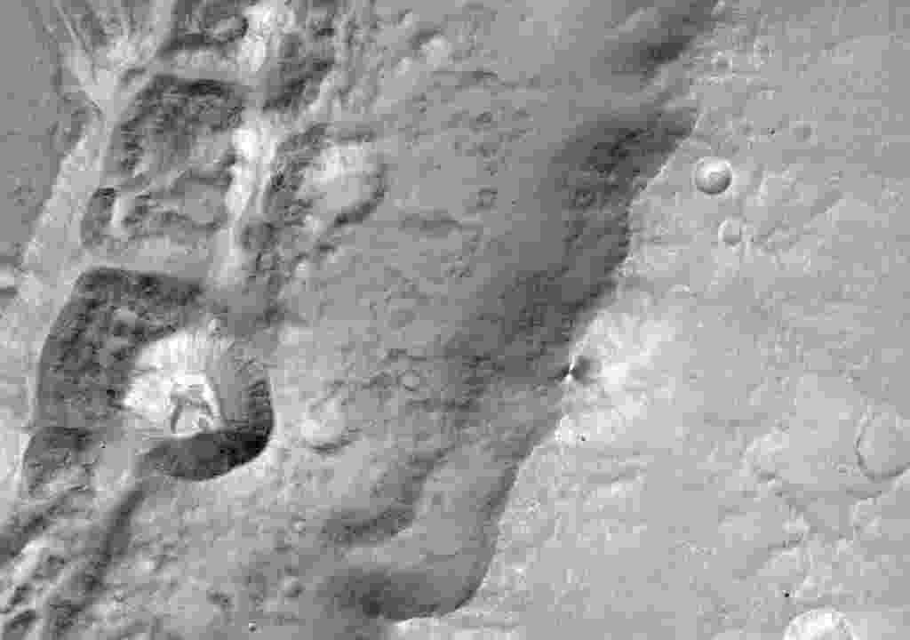 """PRIMEIRAS IMAGENS DA EXOMARS - Cientistas da Agência Espacial Europeia divulgaram uma imagem aproximada de uma cratera chamada """"Da Vinci"""", em Marte. A cratera tem menos de 1,4 km de diâmetro. A imagem foi registrada pelo sistema de imagem Cassis, que foi enviado na missão ExoMar, junto com a sonda Trace Gas Orbiter (TGO). Em outubro a missão teve problemas quando o módulo Schiaparelli caiu no solo do planeta durante o pouso e teve o computador de bordo danificad. O objetivo da TGO é avaliar gases raros na baixa atmosfera de Marte - AFP/European Space Agency"""