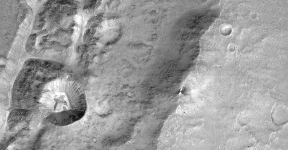 """PRIMEIRAS IMAGENS DA EXOMARS - Cientistas da Agência Espacial Europeia divulgaram uma imagem aproximada de uma cratera chamada """"Da Vinci"""", em Marte. A cratera tem menos de 1,4 km de diâmetro. A imagem foi registrada pelo sistema de imagem Cassis, que foi enviado na missão ExoMar, junto com a sonda Trace Gas Orbiter (TGO). Em outubro a missão teve problemas quando o módulo Schiaparelli caiu no solo do planeta durante o pouso e teve o computador de bordo danificad. O objetivo da TGO é avaliar gases raros na baixa atmosfera de Marte"""