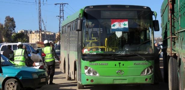 Policiais sírios observam ônibus usado para evacuar rebeldes e civis em Aleppo - AFP