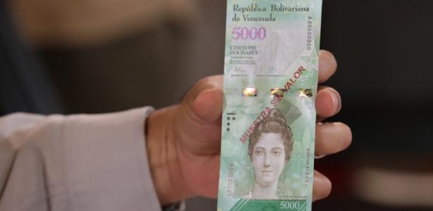 O presidente venezuelano Nicolás Maduro exibe a nova cédula de 5.000 bolívares durante reunião com a equipe econômica