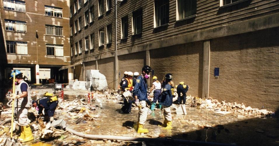 Agentes do FBI limpam uma área do Pentágono alagada após o atentado terrorista que matou 125 pessoas no edifício, entre civis e militares, e os 64 passageiros do voo da American Airlines, incluindo os cinco sequestradores da Al-Qaeda
