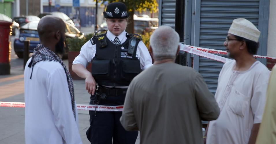 19.jun.2017 - Oficial da polícia fala com moradores da região de Finsbury Park, onde ocorreu o atropelamento de pedestres que saíam de uma mesquita
