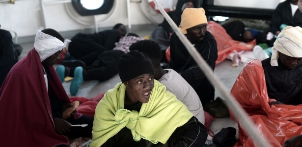 14.jun.2018 - Imigrante come comida fornecida pela guarda-costeira italiana dentro do navio Aquarius