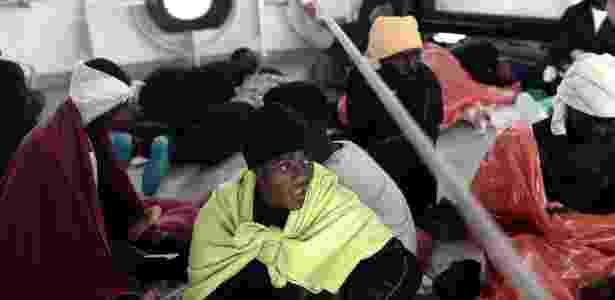14.jun.2018 - Imigrante come comida fornecida pela guarda-costeira italiana dentro do navio Aquarius - Kenny Karpov/SOS Mediterranee/AFP