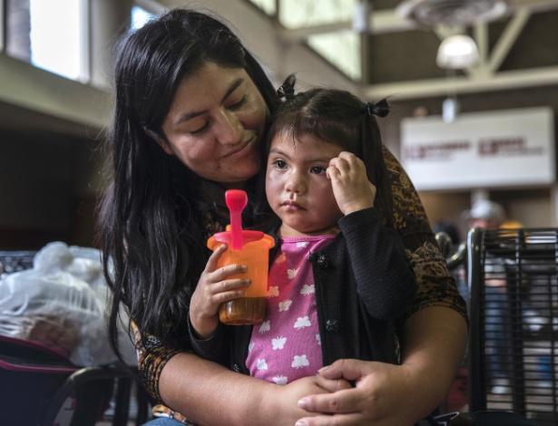 Milka Pablo segura sua filha Darly Coronado, 3, enquanto esperam por um ônibus logo após serem reunidas, na estação de ônibus em Phoenix, Arizona