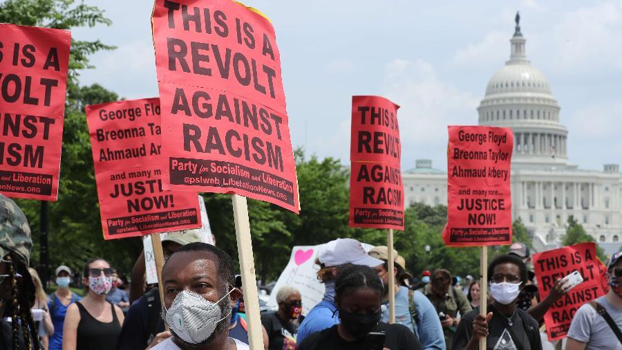 6.jun.2020 - Manifestantes carregam cartazes e se reúnem perto do Congresso dos EUA durante protesto - CHIP SOMODEVILLA/AFP