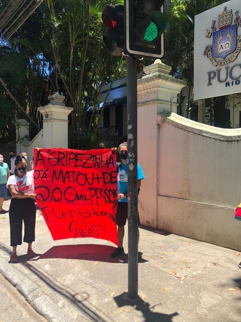 """Um pequeno grupo de manifestantes realizou um protesto em frente a uma das entradas da PUC-Rio (Pontifícia Universidade Católica do Rio), zona sul da cidade. Com um cartaz escrito """"a gripezinha já matou + de 200 mil pessoas"""" decidiram se manifestar contra o presidente Jair Bolsonaro (sem partido) - Tatiana Campbell/UOL"""