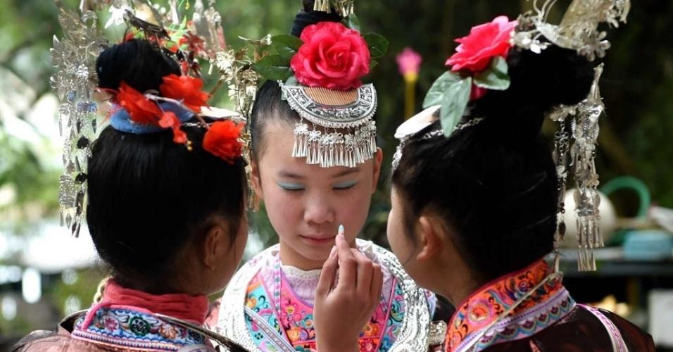 10.mar.2016 - Mulheres da etnia Dong se preparam para desfile que celebra o segundo dia do segundo mês do calendário lunar da China, em Meilin, no sul do país