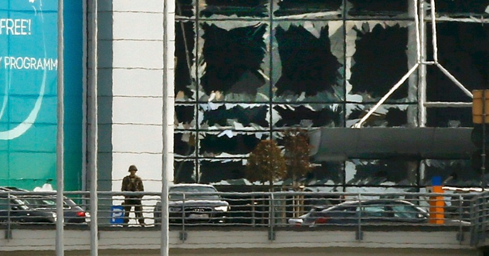 22.mar.2016 - Soldado faz vigília em frente às janelas quebradas após atentado na área de embarque do aeroporto internacional de Bruxelas
