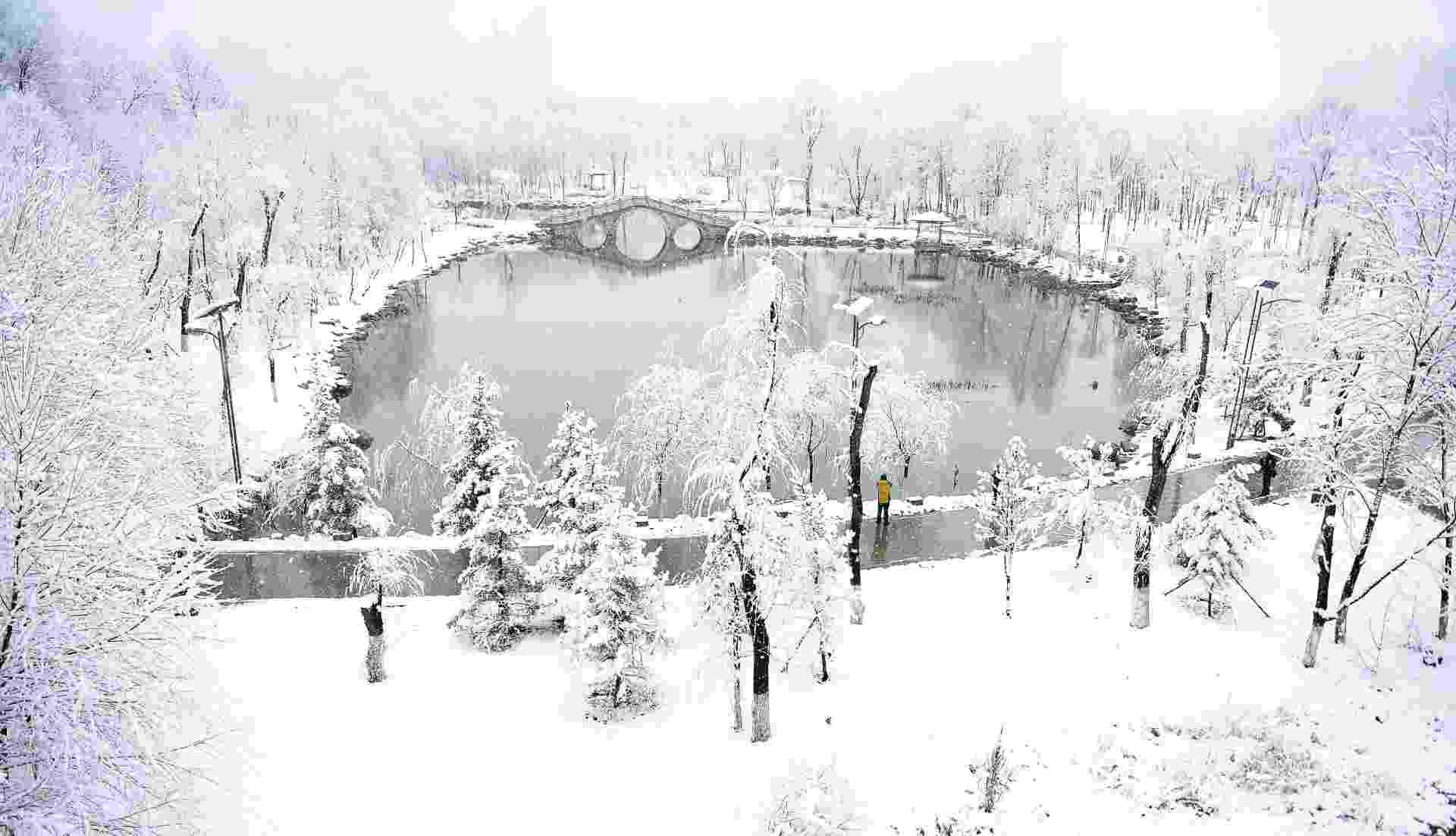 24.mar.2016 - Parque amanhece coberto de neve em Xining, no noroeste da China. Uma forte nevasca atingiu grande parte da província de Qinghai, onde está localizada a cidade, durante esta madrugada - undefined