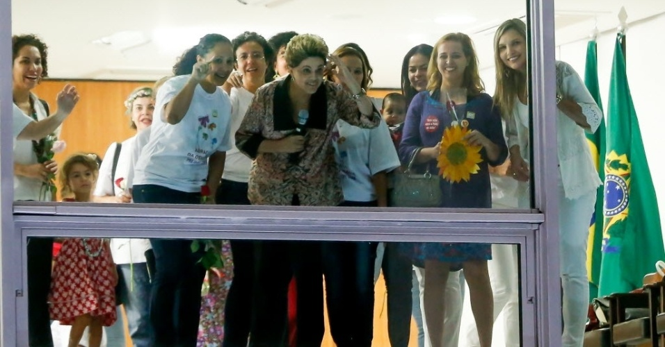 19.abr.2016 - A presidente Dilma Rousseff observa de uma janela o ato de mulheres que foram ao Palácio do Planalto, em Brasília (DF), oferecer flores e declarar apoio a ela no processo do impeachment