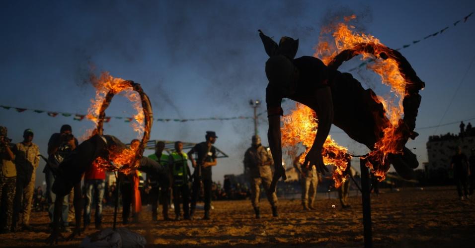 22.jul.2016 - Jovens mostram suas habilidades com fogo durante cerimônia de formatura de um acampamento militar de verão organizado pelo grupo Hamas na cidade de Gaza, Palestina