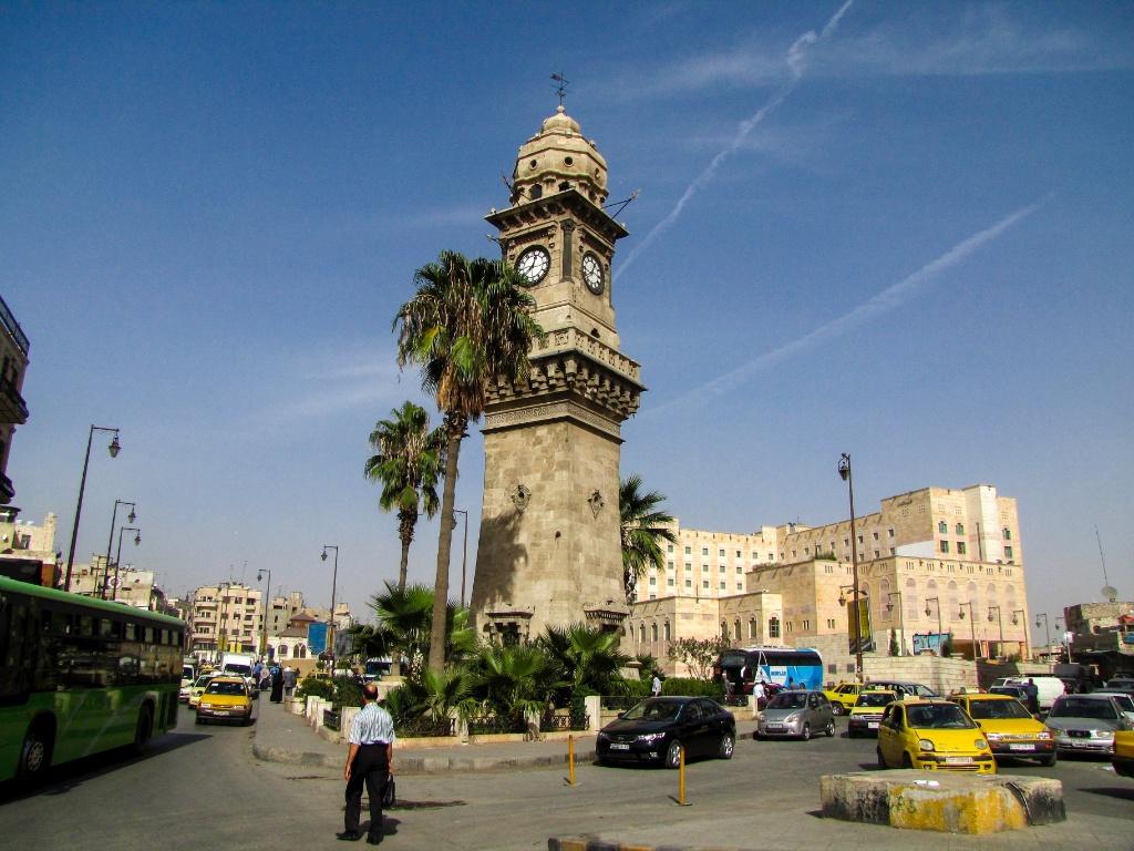 Veículos transitam ao redor da famosa ?Torre do Relógio? em rua movimentada de Aleppo