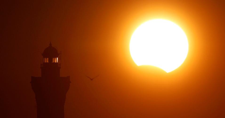 21.ago.2017 - O farol de Eckmuehl é iluminado com luz do pôr-do-sol durante um eclipse solar parcial em Penmarc'h, Bretanha (França)