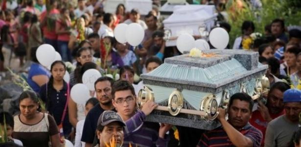 Depois da tragédia na igreja, familiares e amigos da família realizam um enterro coletivo na cidade - Reuters