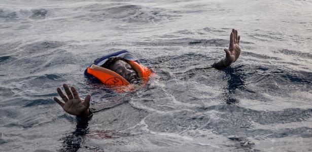 Migrante tenta não afundar enquanto aguarda o resgate da ONG Sea Watch no mar Mediterrâneo