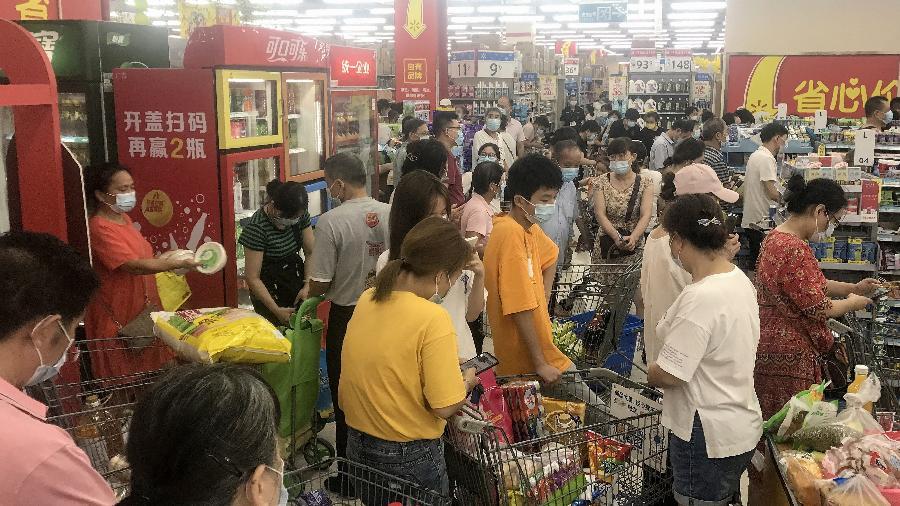2.ago.2021 - Pessoas comprando itens em supermercado em Wuhan, na China, enquanto as autoridades disseram que testariam toda a população para covid-19 - STR/AFP