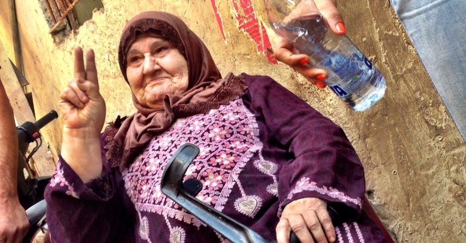 Mulher refugiada palestina octogenária faz o sinal da vitória em uma miserável viela do campo de Chatila, no Líbano