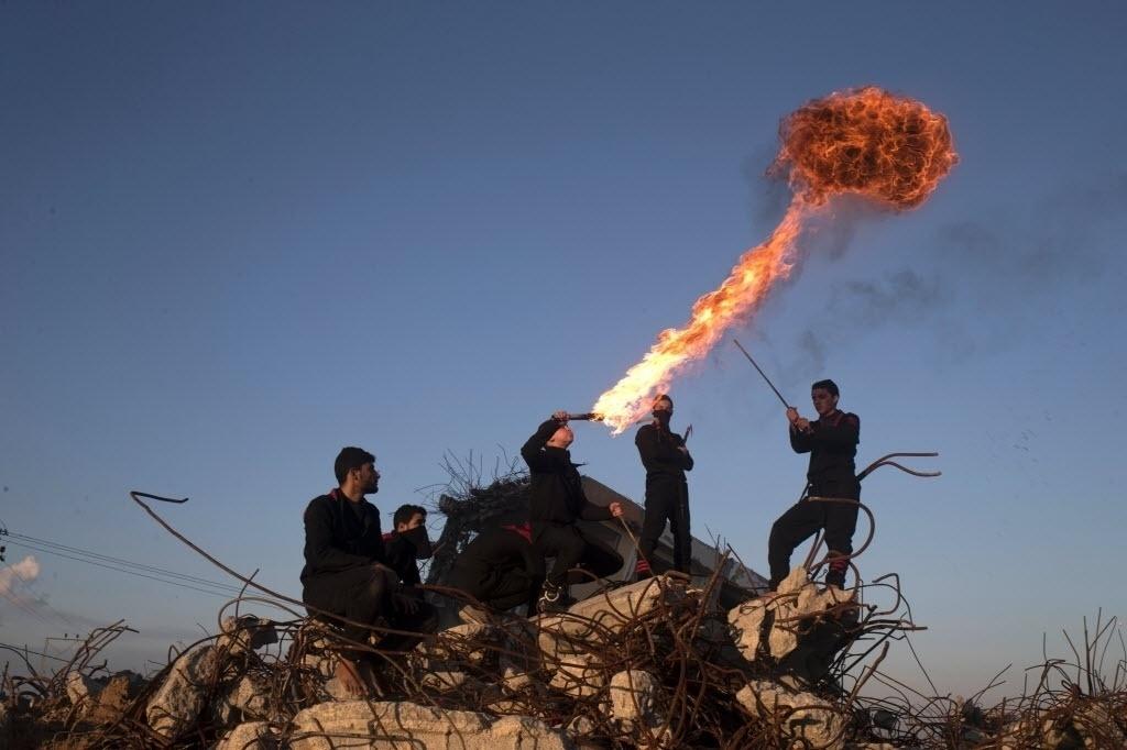 11.fev.2016 - Jovens palestinos de um grupo de artes marciais fazem uma apresentação com fogo no meio das ruínas das casas que foram destruídas durante a guerra em 2014, entre Israel e o Hamas, no norte da Faixa de Gaza